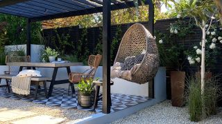 an outdoor seating area with hanging chair