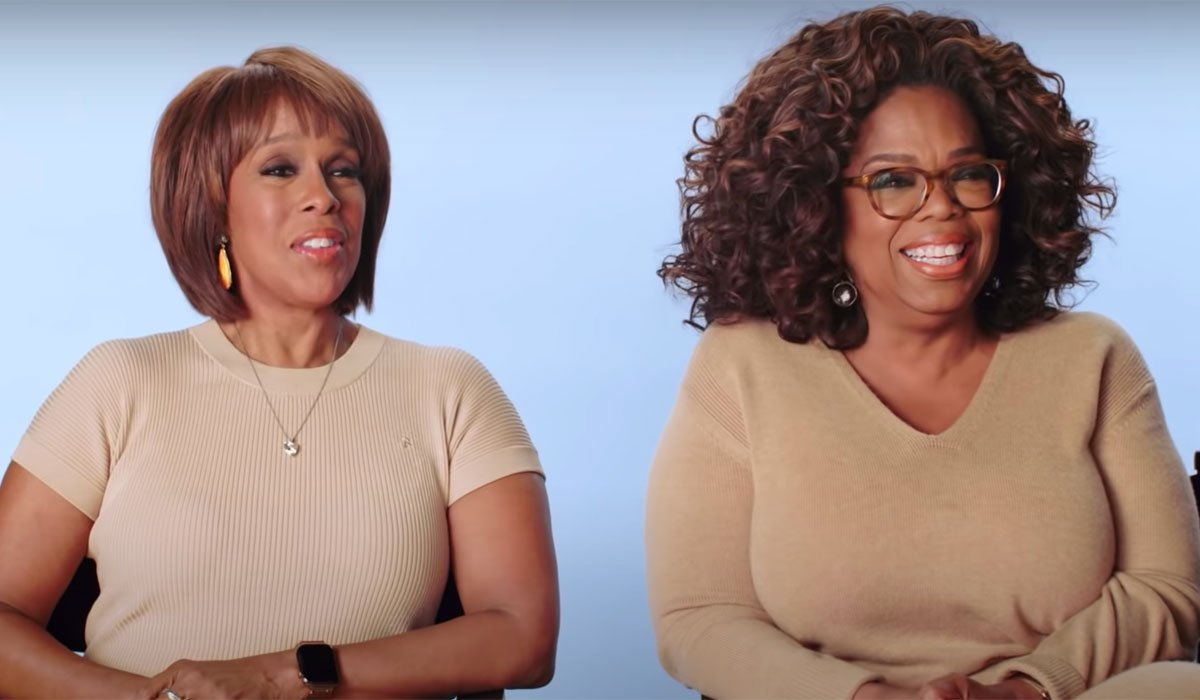 Oprah Winfrey and Gayle King laugh and sit next to each other in chairs during an interview.