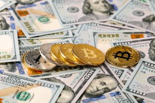 Image of Bitcoin on top of US Dollars.