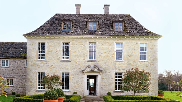 exterior of classic Cotswold stone Georgian style newbuild country house