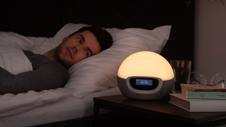 Man lying in bed looking at Lumie Bodyclock Shine 300 wake up light, which is on dim