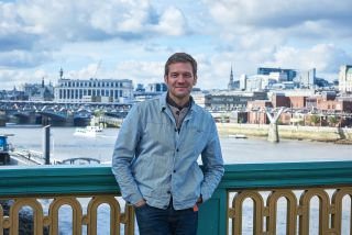 Charlie Luxton standing on a bridge over the Thames