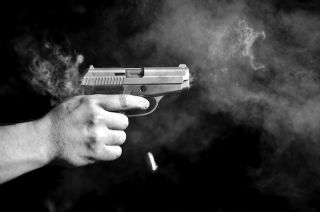 Firing a handgun in black and white