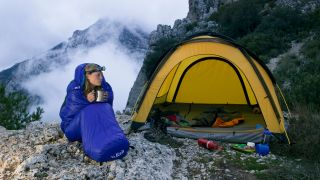 Best women's sleeping bags: A woman curled up in a sleeping bag on a mountain