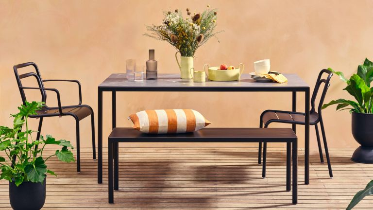 A black metal outdoor dining set against a terracotta outdoor wall