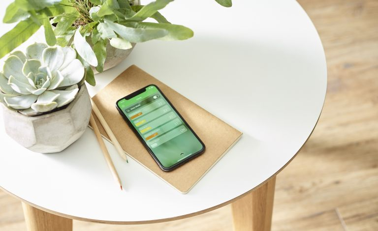 Wiser app on a phone on a table for smart heating