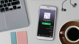 Spotify app on smartphone, on desk with laptop, earbuds and coffee