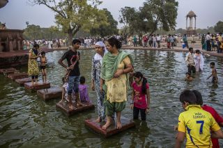 Families cool off in a pond during a heat wave on June 2, 2012, in New Delhi, India.