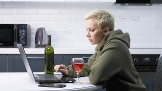 A woman is using laptop and drinking wine , in the kitchen.