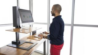 Man using a desktop PC on one of the best standing desks featured in this article.