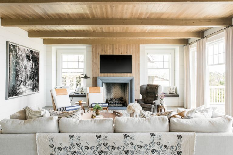 TV wall idea in a Living room with mostly muted colors and natural wood with pops of mustard and patterns
