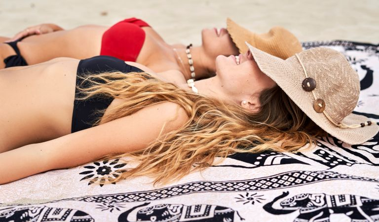 Two young women lying on a towel a beach - TikTok Towel challenge solved