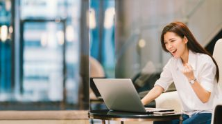 Glad kvinna som använder en bärbar dator