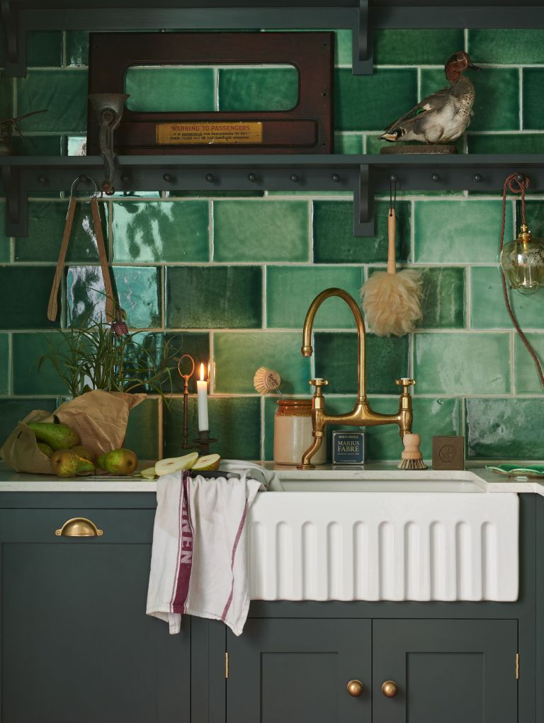 Matt black base cabinets and different shades of green tiles