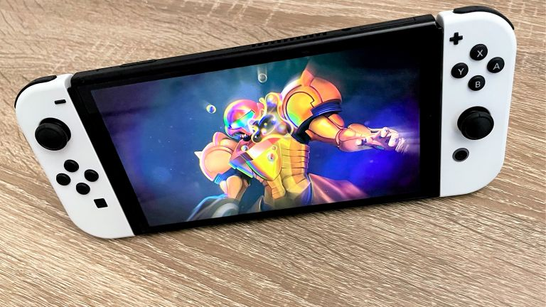 Nintendo Switch OLED on wooden surface, with Metroid Dread on the screen
