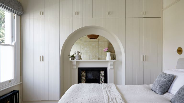 White bedroom with wall of built in storage over fireplace