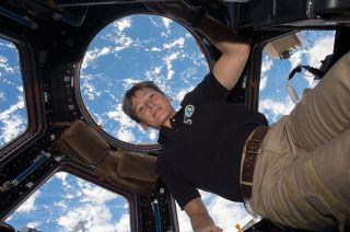 Astronaut Peggy Whitson floats in the cupola on board the International Space Station, backdropped by the Earth below.