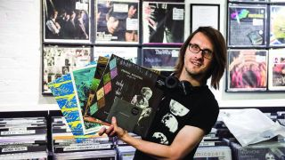 a shot of steven wilson holding a bunch of records