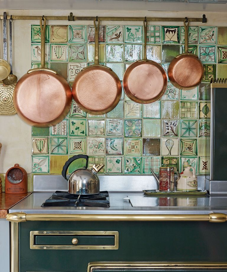 tiled patterned backsplash in a country rustic farmhouse kitchen with green range cooker and copper cooking pans - Credit-tiled-splashback-Future