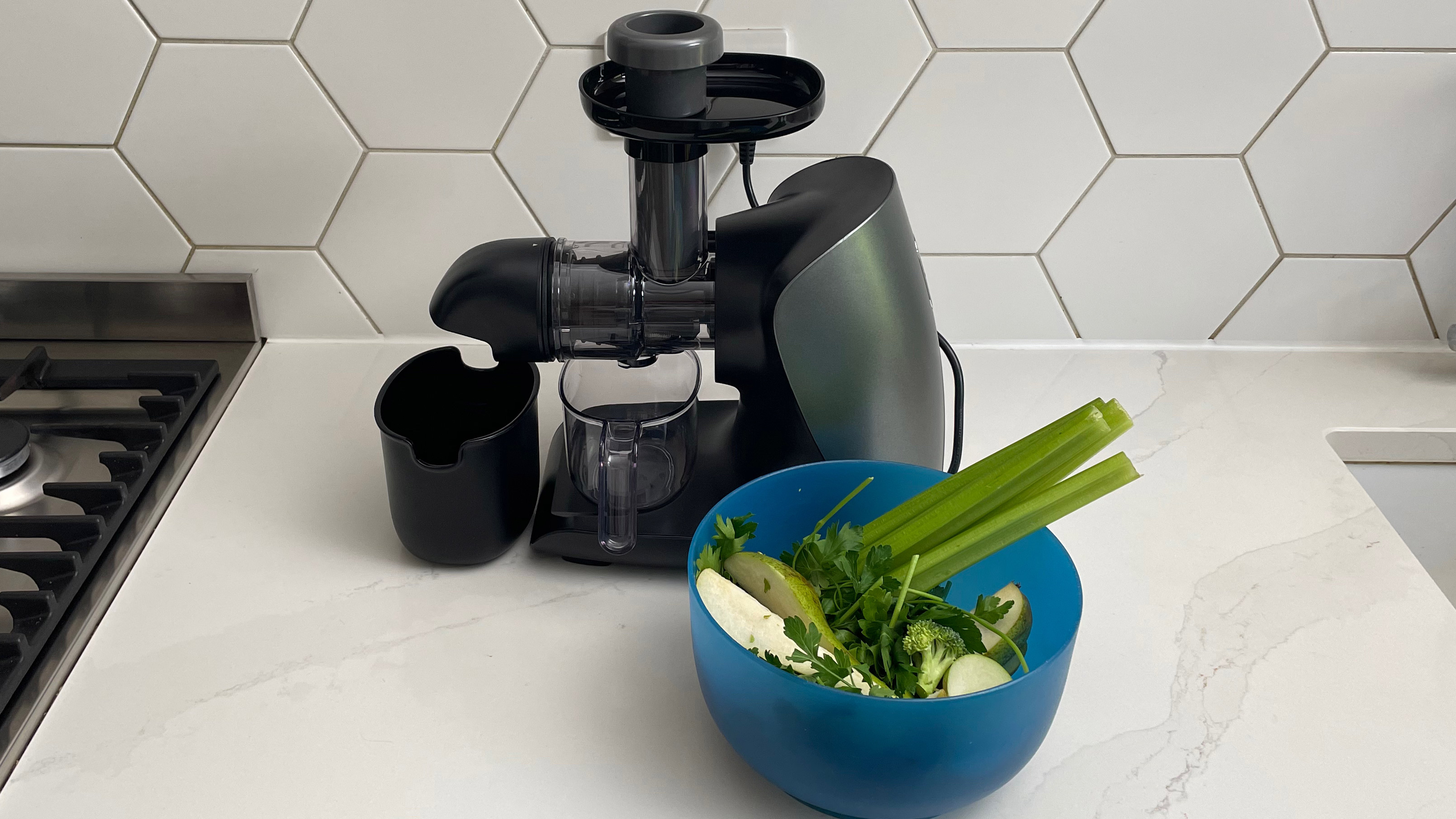Ninja Cold Press Juicer with a selection of green fruit and vegetables ready to be juiced