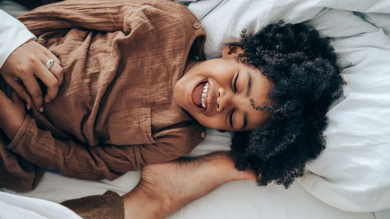 best kids mattress: Happy boy lying on bed with adults foot playfully tapping his head