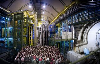 The LHCb team stands in front of their experiment, the LHCb detecor, at the Large Hadron Collider in Geneva.