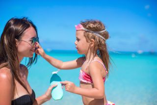 girl applying sunscreen to mom on beach