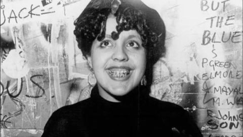 A black and white photo shows punk icon Poly Styrene standing against a wall covered in grafitti
