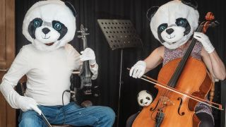 Two people in panda suits playing instruments