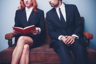 businessman looking at woman's book.