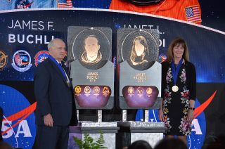 Astronauts Jim Buchli and Janet Kavandi were inducted into the U.S. Astronaut Hall of Fame during a ceremony on Saturday, April 6, 2019, under the display of the retired space shuttle Atlantis at NASA's Kennedy Space Center Visitor Complex in Florida. They unveiled their plaques, which will be placed in the Hall of Fame at the visitor complex.