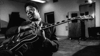 Black and white photo of BB King sat down holding his Gibson guitar
