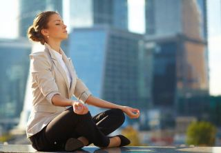 woman meditates in city