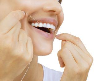 A woman flosses her teeth