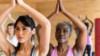 Yoga myths: Two women, one younger and one older, raise their arms in a yoga pose