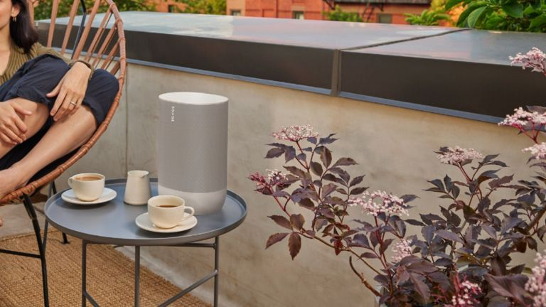 best smart speaker: Sonos Move placed on outdoor table beside woman sitting in chair