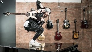 a shot of Justin Hawkins crouching on a grand piano holding a guitar