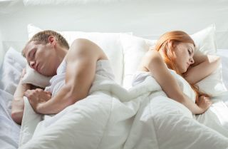 A man and a woman lie sleeping in a bed.
