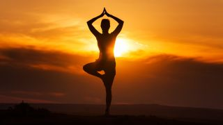 Is yoga a religion? image shows woman doing tree pose before a sunset