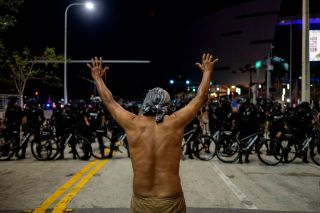 A protester holds up his hands in front of a row of police officers during a rally in response to the recent death of George Floyd an unarmed black man who died while in police custody in Minneapolis in Miami Florida on May 31 2020 Thousands of National Guard troops patrolled major US cities after five consecutive nights of protests over racism and police brutality that boiled over into arson and looting sending shock waves through the country The death Monday of an unarmed black man George Floyd at the hands of police in Minneapolis ignited this latest wave of outrage in the US over law enforcements repeated use of lethal force against African Americans this one like others before captured on cellphone video Photo by Ricardo ARDUENGO AFP Photo by RICARDO ARDUENGOAFP via Getty Images