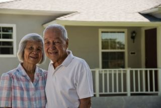 Elderly asian couple in front of their home.