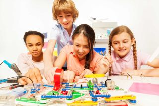 Four students test electric circuits in the classroom lab