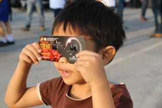 March 9, 2016: Thailand boy viewing a solar eclipse in Chiang Mai, Thailand.