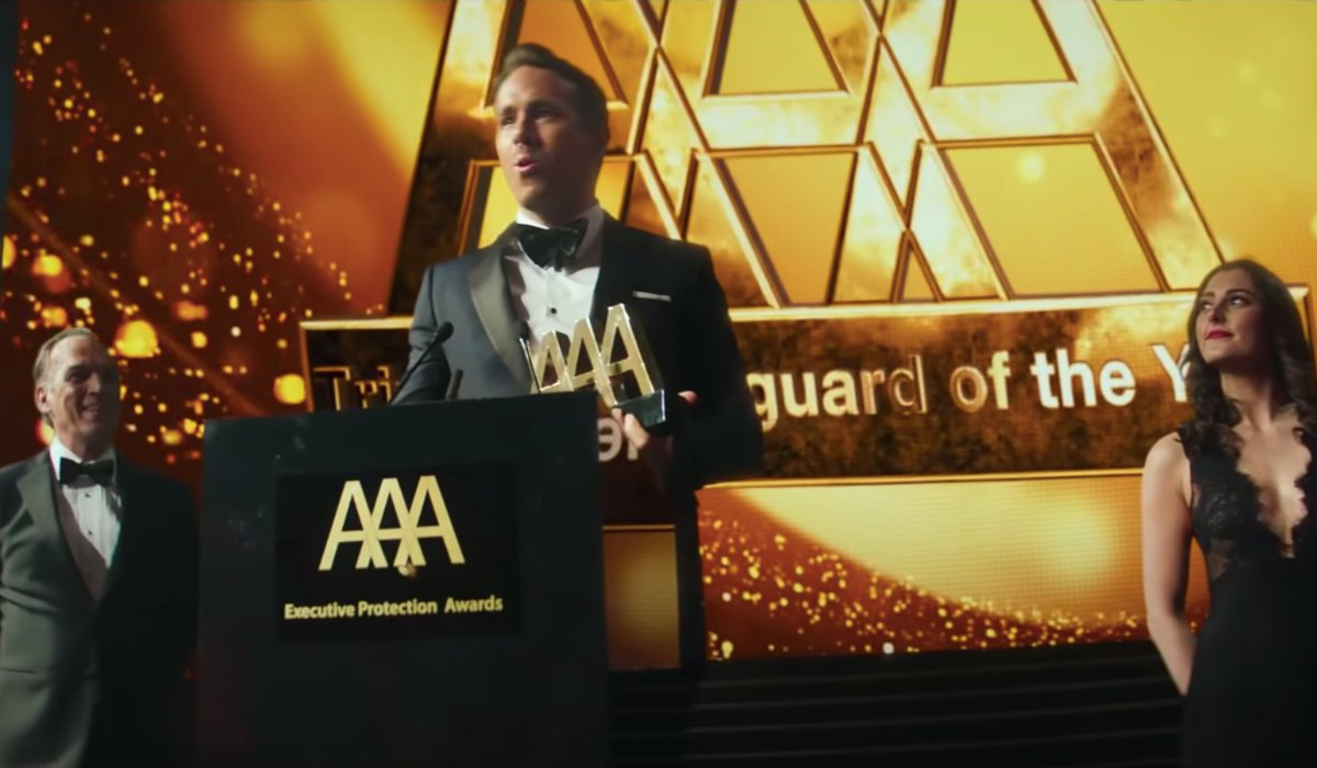 Ryan Reynolds accepts an award with excitement in The Hitman's Wife's Bodyguard.