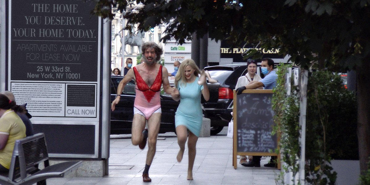 Borat and Tutar run through the streets following her interview with Rudy Giuilani in 'Borat 2'
