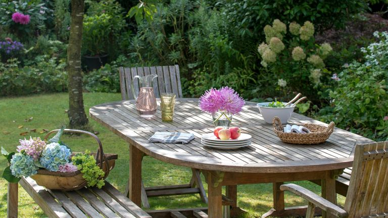 budget backyard ideas wooden table on lawn with picked flowers