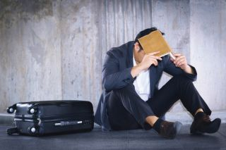 Stressed businessman sitting on ground with suitcase.