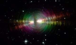 """The Egg Nebula, seen here in a view from the Hubble Space Telescope, is a """"preplanetary nebula,"""" or a cloud of dust and gas ejected from a dying star and illuminated by the star's last bit of light."""