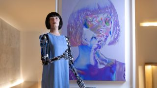 """The robot artist """"Ai-Da"""" stands in front of one of her self-portraits during the opening of her new exhibition at the Design Museum in London on May 18."""