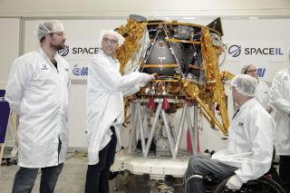 Yonatan Winetraub, one of three SpaceIL founders, inserts a time capsule into the compay's private moon lander, which is scheduled to launch in February 2019.